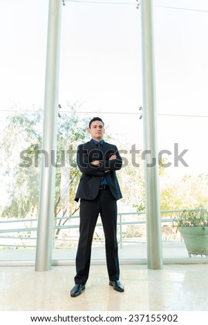 Portrait of a young man in a suit standing inside a large office - stock photo