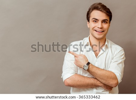 Portrait of a young man in a white shirt, pointing a finger toward, the clock on the hand, �¿�¾���¼�?�?�°�?�?�¸���?, on gray background
