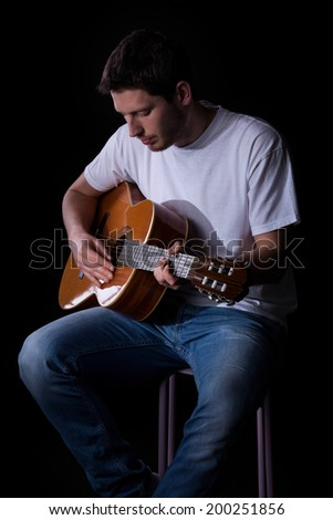 Portrait of a young man in casual clothes playing guitar - stock photo
