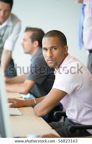Portrait of a young man in front of a computer - stock photo