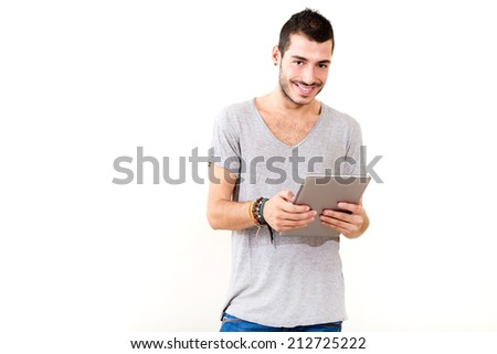Portrait of a young man in grey shirt using tablet.  - stock photo