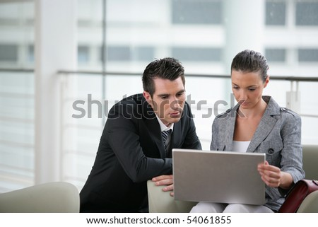 Portrait of a young man in suit and a young woman with a laptop computer - stock photo