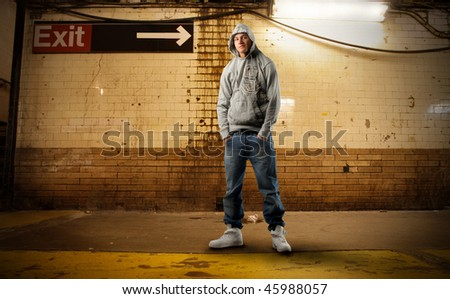 Portrait of a young man in trendy clothes standing on a city street - stock photo