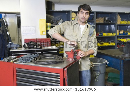 Portrait of a young man in workshop with tools