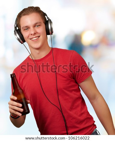 portrait of a young man listening to music and holding a beer indoor - stock photo