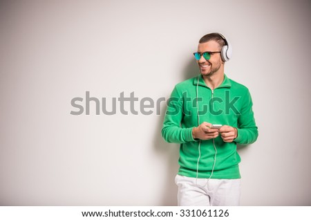 Portrait of a young man listening to music in headphones on gray background - stock photo
