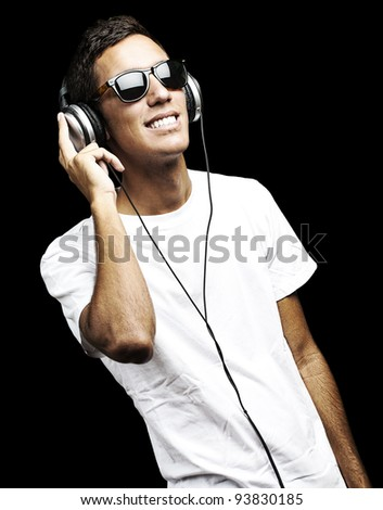 portrait of a young man listening to music with headphones against a black background - stock photo