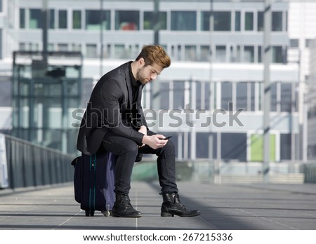 Portrait of a young man looking at mobile phone. Male traveler sitting on suitcase reading text message - stock photo
