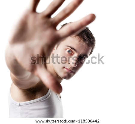Portrait of a young man looking out from under raised hand on a light background