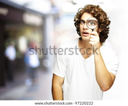 portrait of a young man looking through a magnifying glass at a crowded place - stock photo