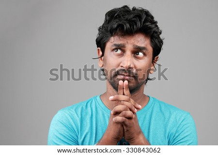 Portrait of a young man looks up in a confused state - stock photo