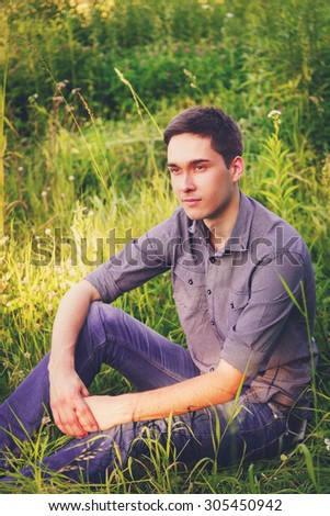 Portrait of a young man on nature in the grass