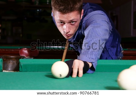 portrait of a young man playing billiards