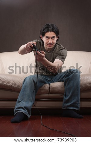 portrait of a young man playing video games on gray background