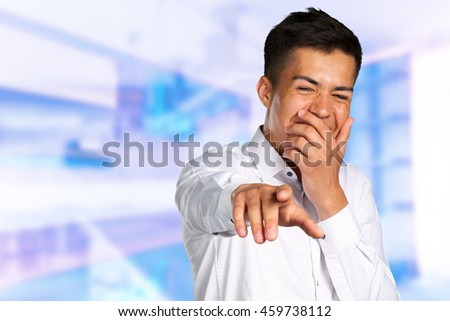 Portrait of a young man pointing his finger at you - stock photo