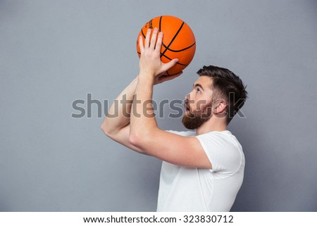 Portrait of a young man reading to throw basket ball over gray background - stock photo
