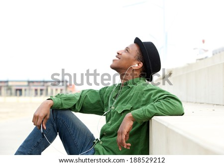 Portrait of a young man relaxing outdoors and listening to mp 3 player - stock photo