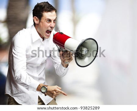 portrait of a young man screaming with a megaphone against a street background - stock photo