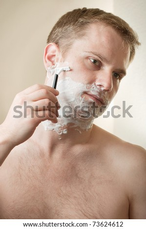 Portrait of a young man shaving - stock photo