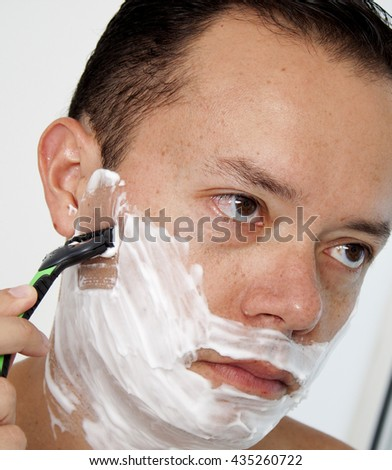 Portrait of a young man shaving his beard with razor - stock photo