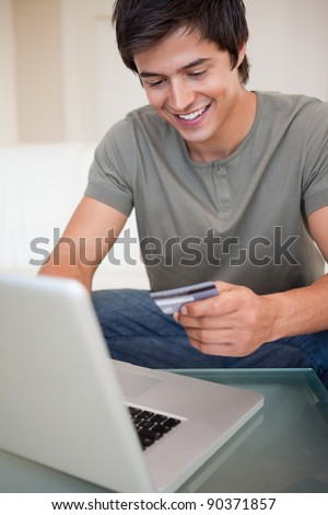 Portrait of a young man shopping online in his living room - stock photo