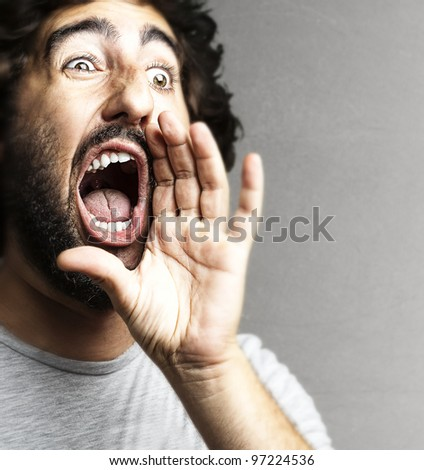 portrait of a young man shouting against a grey background - stock photo