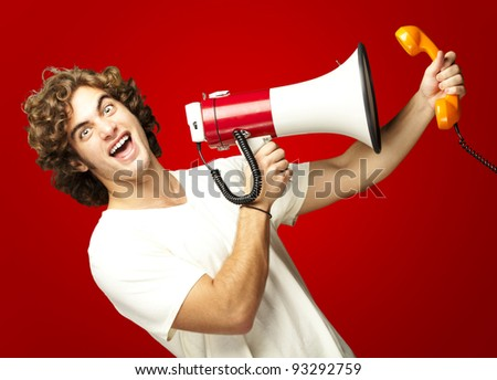 portrait of a young man shouting with a megaphone and talking on a vintage telephone over a red background - stock photo