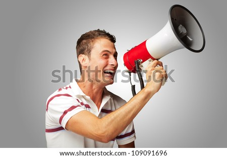 Portrait Of A Young Man Shouting With Megaphone On Gray Background - stock photo