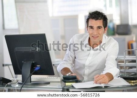 Portrait of a young man sitting at a desk typing on a calculator