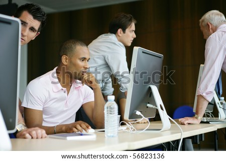 Portrait of a young man sitting in front of a desktop computer - stock photo