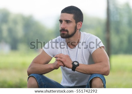 Portrait Of A Young Man Sitting on Grass - Handsome Guy Repose in Nature - Outdoors - Outside