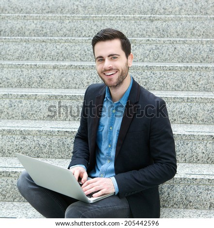 Portrait of a young man sitting on steps and smiling with laptop - stock photo