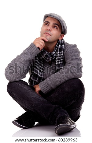 Portrait of a young man sitting on the floor, thinking and looking up, in autumn/winter clothes, isolated on white, Studio shot - stock photo