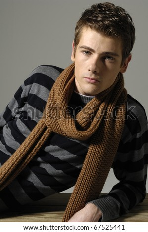 Portrait of a young man sitting wearing scarf on the floor
