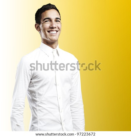 portrait of a young man smiling against a yellow background - stock photo