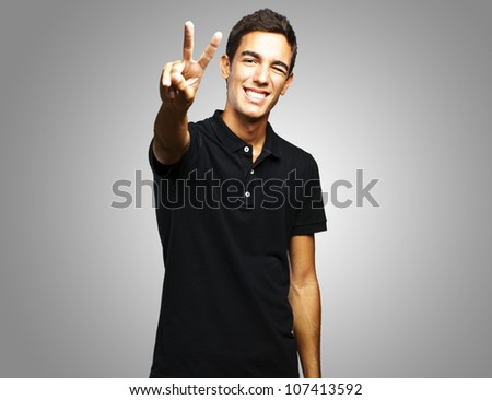portrait of a young man smiling and doing a good symbol against a grey background - stock photo