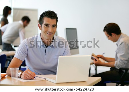 Portrait of a young man smiling in front of a laptop computer - stock photo