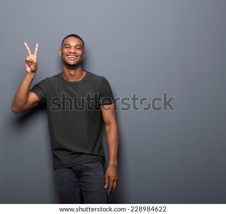 Portrait of a young man smiling showing hand peace sign - stock photo