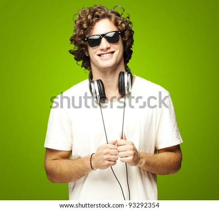 portrait of a young man smiling with headphones over a green background