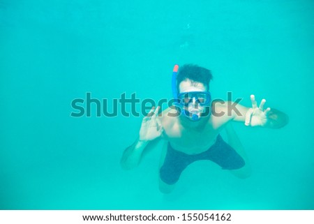 Portrait of a young man snorkeling in a blue clean water - stock photo