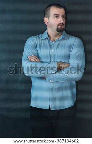 portrait of a young man standing posing in the shadows from blinds in the dark room