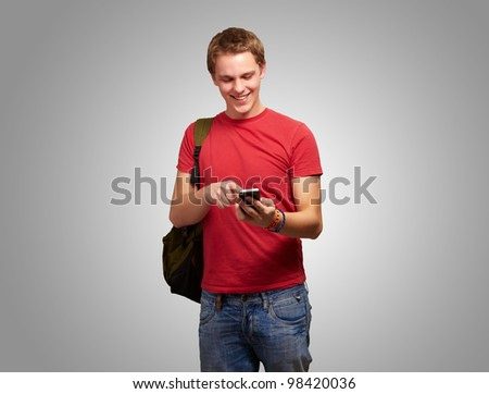 portrait of a young man touching a mobile screen over a grey background