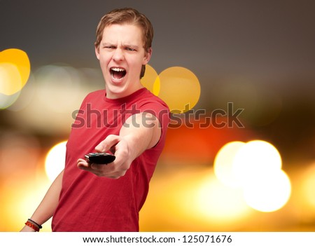 portrait of a young man using remote control, background - stock photo