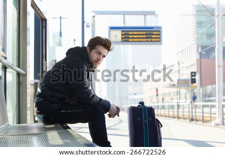 Portrait of a young man waiting for train with suitcase travel bag - stock photo