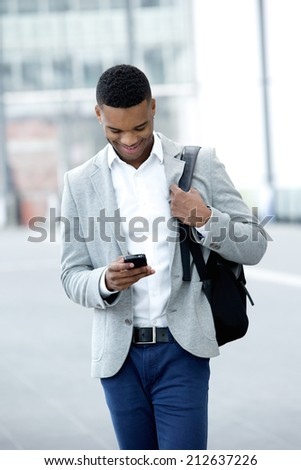 Portrait of a young man walking and looking at mobile phone - stock photo