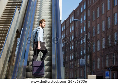 Portrait of a young man walking up escalator with travel bags - stock photo