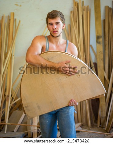 Portrait of a young man who keeps working wood products - stock photo