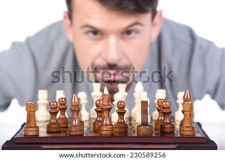 Portrait of a young man with a chess on a white background. Close-up. - stock photo