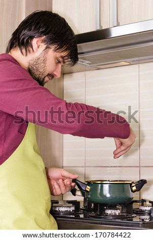 Portrait of a young man with apron seasoning meal with salt at home - stock photo