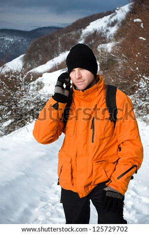 Portrait of a young man with backpack speaking on mobile phone. Snowy mountain landscape as a background. - stock photo
